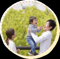 子供を抱いて笑顔でいる家族