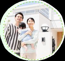 写真:家の前に立つ子供を抱えた夫婦