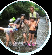 川で記念撮影している家族